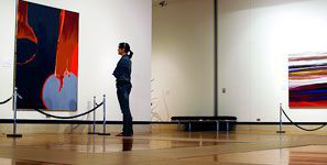 Student looking at painting in gallery